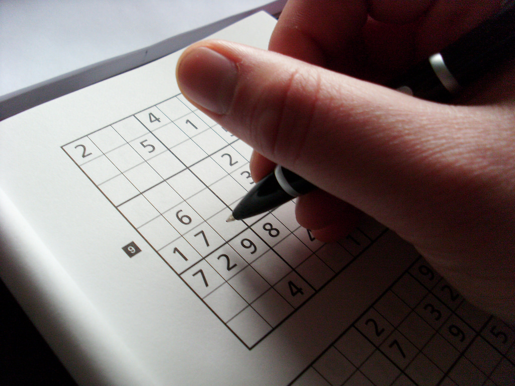 Man Writing His Answers on a Sudoku Sheet Using Ballpen for 247 Sudoku Relaxation Game