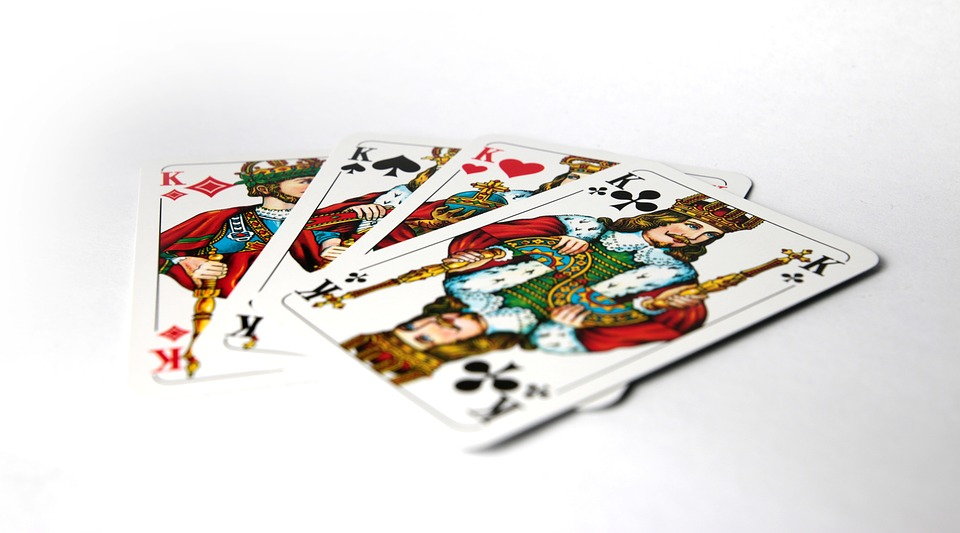 Four King Cards on a White Table used for Playing Kings Corner Card Game