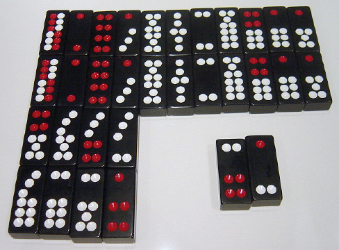Photo of a set of Chinese dominoes The top double row of tiles lists the eleven matching pairs in descending value from left to right for Pai Gow Poker Game