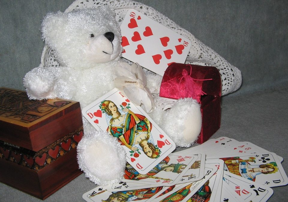 teddy bear besides playing cards
